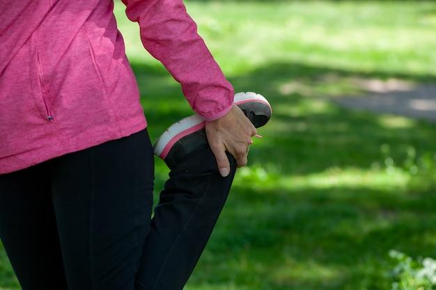 Une femme mûre s'entraîne dans un parc en faisant des étirements portant un masque chirurgical pendant la pandémie de covid