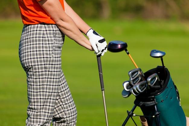 Femme mûre avec sac de golf jouant au golf