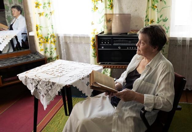 Femme mûre se reposant dans un fauteuil dans le salon avec un design d'intérieur du milieu du siècle, un livre de lecture féminin...