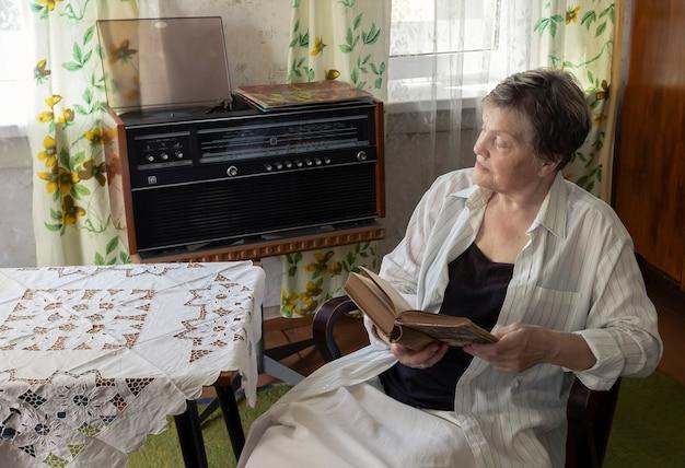 Femme mûre se reposant dans un fauteuil dans un salon avec des meubles du milieu du siècle et un design d'intérieur féminin...