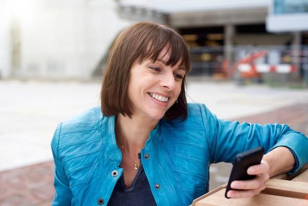 Femme mûre en souriant et en regardant le téléphone mobile