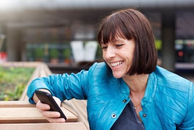 Femme mûre en souriant et en regardant le téléphone portable