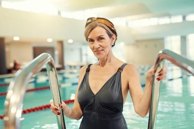 Femme mûre souriante, entrer, piscine