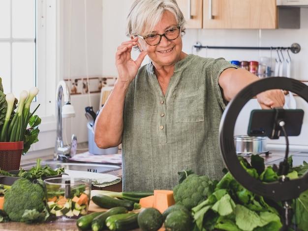 Femme mûre suivant le cours de cuisine en ligne, blogueur, vidéo - régime végétalien végétarien