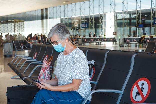 Femme mûre de voyageur s'asseyant dans l'aéroport avec des bagages utilisant le téléphone portable attendant le départ du vol. concept de coronavirus et de liberté