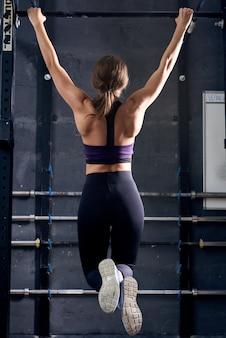Femme musclée faisant des tractions dans le gymnase crossfit
