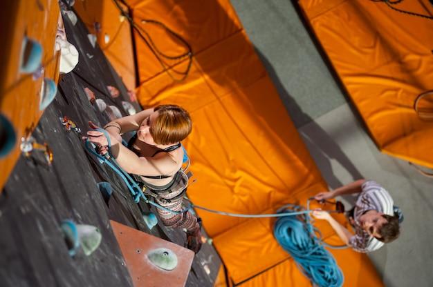 Une femme musclée grimpe avec des carabines et une corde sur un mur d'escalade intérieur.