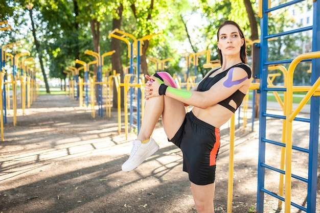 Femme musclée magnifique flexible portant une tenue de sport noire, étirement de la jambe et jeune athlète féminine brune confiante pratiquant la gymnastique,