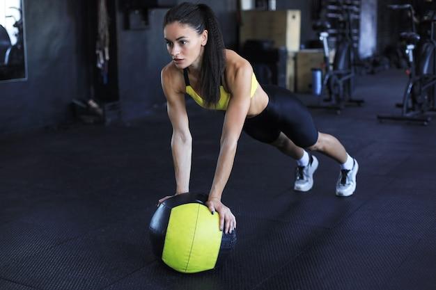 Une femme musclée s'entraîne avec un ballon de médecine dans une salle de sport.