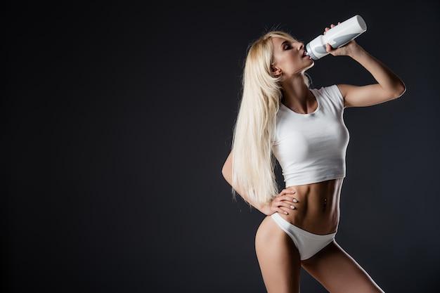 Femme musclée sportive eau potable, isolée contre gris