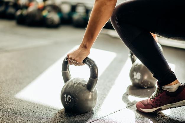 Femme musclée tenant une cloche de bouilloire ancienne et rouillée sur le sol de la salle de gym