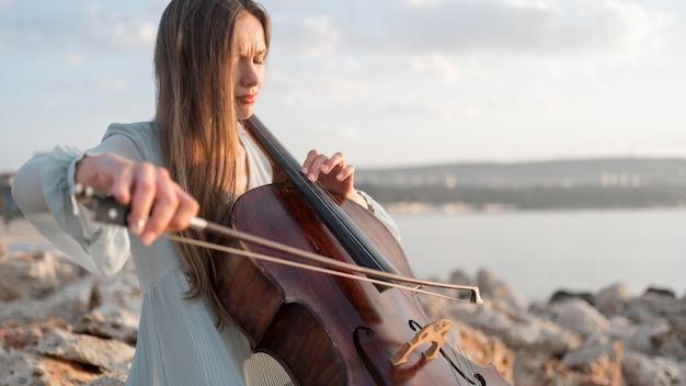 Femme musicienne jouant du violoncelle au coucher du soleil avec copie espace