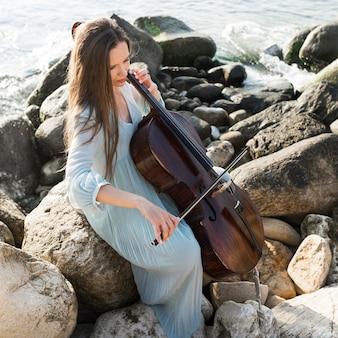 Femme musicienne sur des rochers à jouer du violoncelle au bord de la mer