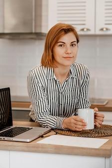 Femme musicienne smiley à la maison avec tasse et ordinateur portable
