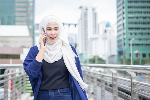 Femme musulmane d'affaires utilisant le téléphone en ville.