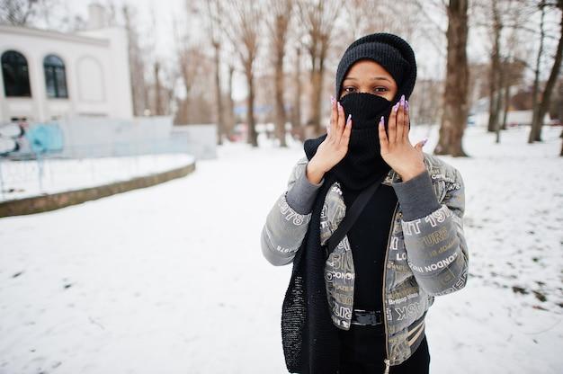 Femme musulmane africaine porter en foulard hijab noir pose en journée d'hiver