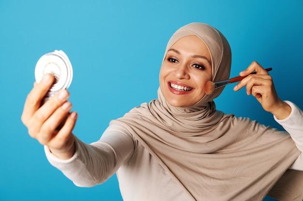 Femme musulmane arabe avec couvert en regardant miroir et en appliquant le maquillage, isolé