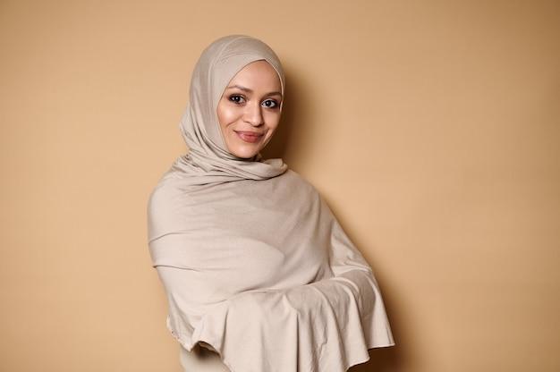 Femme musulmane arabe dans des vêtements religieux stricts et la tête couverte de hijab, cute smiling looking at camera