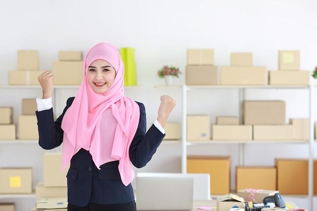 Femme musulmane asiatique en costume bleu et arbre rose debout et regardant la caméra avec une émotion excitante.