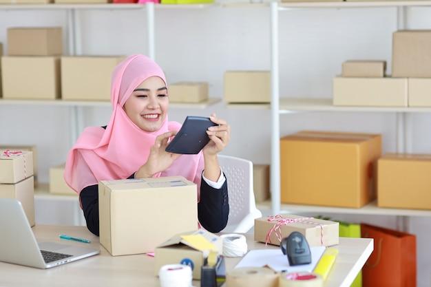 Femme musulmane asiatique en costume bleu assis et travaillant avec la livraison de boîte de colis en ligne.