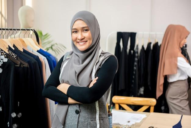 Femme musulmane asiatique dans son atelier de couture