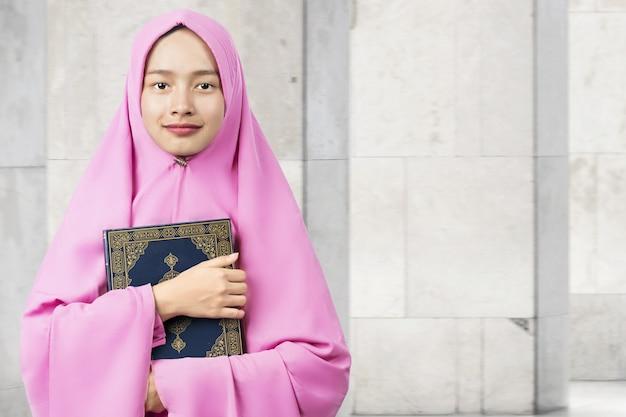 Femme musulmane asiatique dans un voile debout et tenant le coran