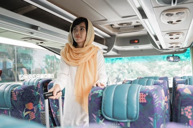 Femme musulmane asiatique faisant le voyage de retour dans sa ville natale en prenant un bus