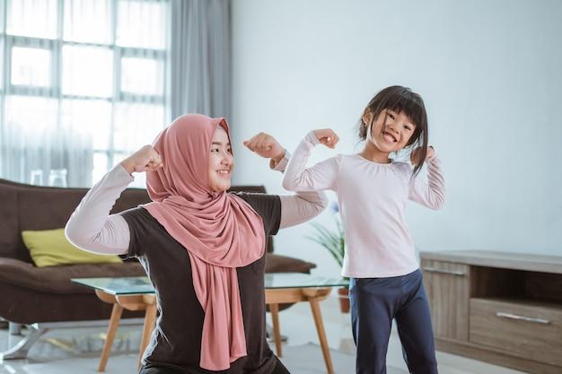 Femme musulmane asiatique et fille faisant de l'exercice et du sport à la maison pendant l'auto-isolement