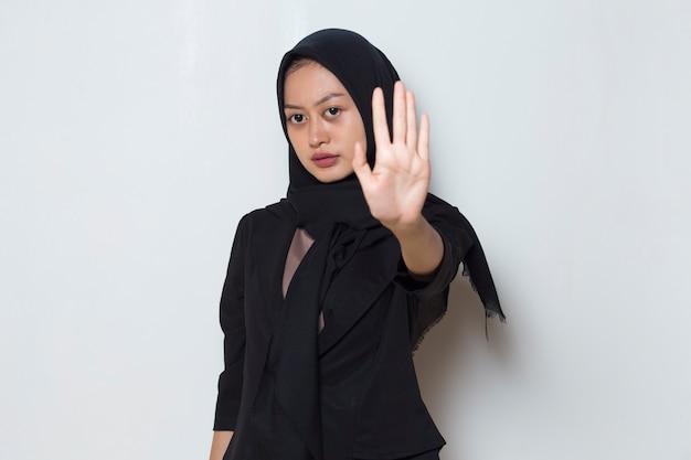La femme musulmane asiatique de hijab montre le geste de mains d'arrêt