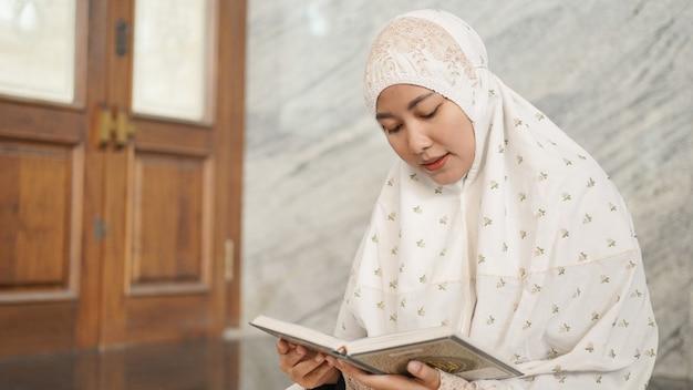 Femme musulmane asiatique lisant le coran dans la mosquée