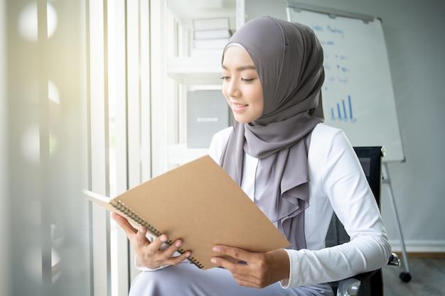 Femme musulmane asiatique lisant un livre au bureau. concept de mode de vie des musulmans modernes, portrait du musulman.
