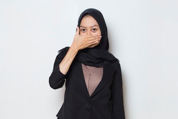 La femme musulmane asiatique a mis sa main pour couvrir sa bouche