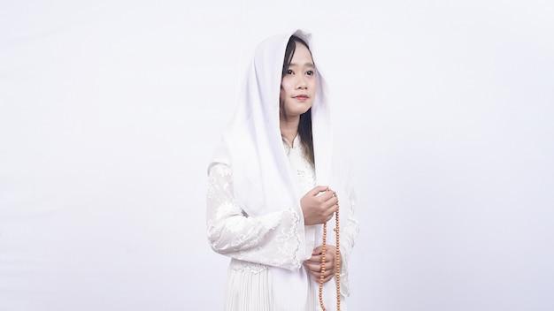 Femme musulmane asiatique portant un chapelet prier avec tasbih en blanc