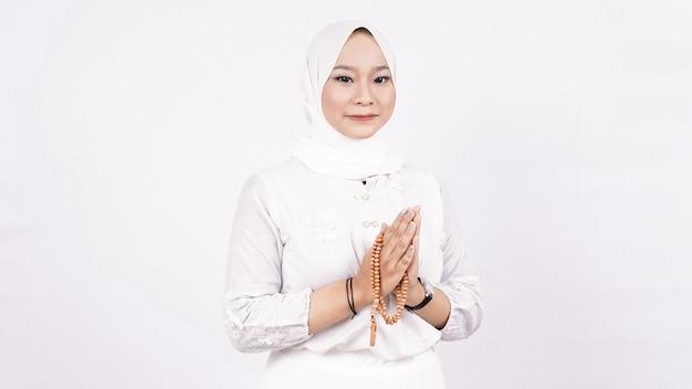 Femme musulmane asiatique portant des perles de prière accueillant les invités ou ied fitr voeux dans l'espace blanc