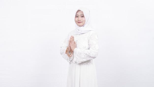 Femme musulmane asiatique portant des perles de prière accueillant des invités