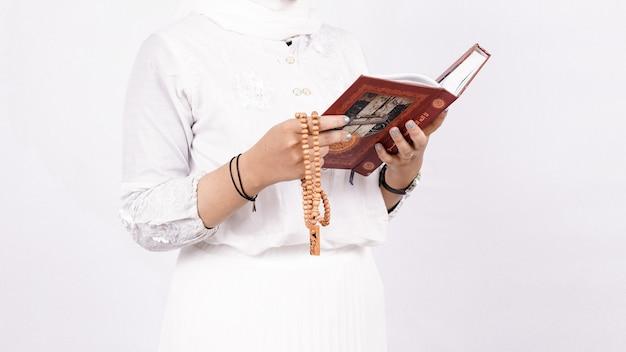 Femme musulmane asiatique portant des perles de prière prient dans l'espace blanc