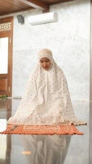 Femme musulmane asiatique priant dans la mosquée