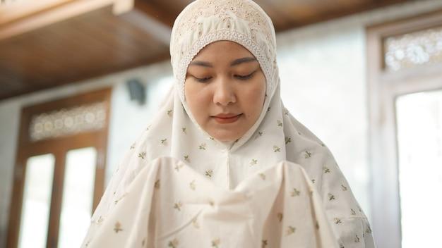 Femme musulmane asiatique priant avec espoir dans la mosquée