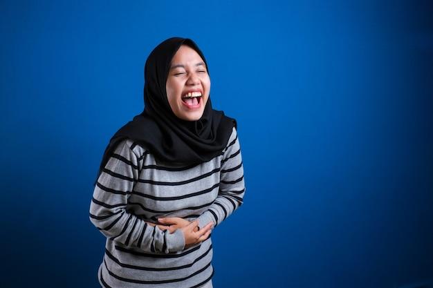 Femme musulmane asiatique riant fort tout en tenant son ventre, expression heureuse et excitée sur fond bleu