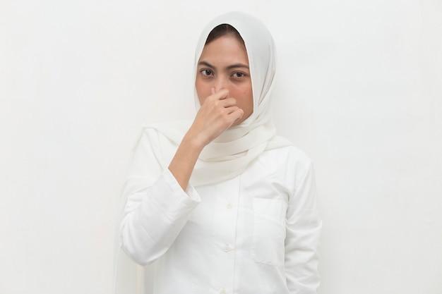 Femme musulmane asiatique tenant son nez à cause d'une mauvaise odeur