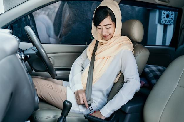 Femme musulmane attache sa ceinture de sécurité