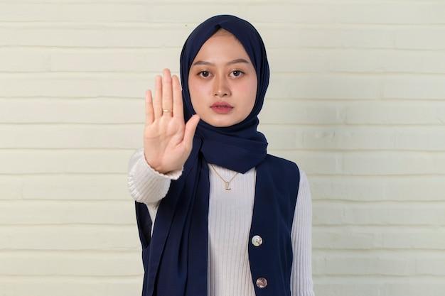 Femme musulmane bouleversée grave montrant le geste de la main d'arrêt