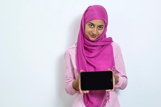 Une femme musulmane dans un hijab tient une tablette.