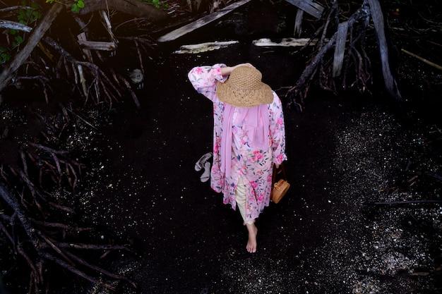 Femme musulmane debout sur la plage de sable noir en vacances, touriste asiatique marchant sur fond sombre.