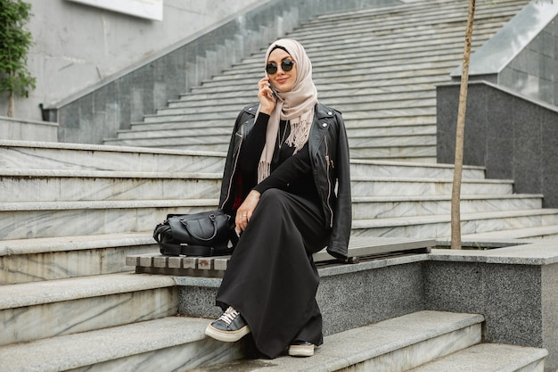 Femme musulmane élégante moderne en hijab, veste en cuir et abaya noire marchant dans la rue de la ville parlant sur smartphone