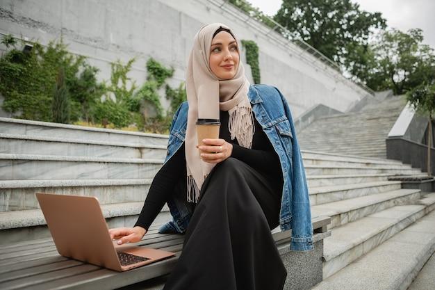Femme musulmane élégante moderne en hijab, veste en jean et abaya noire assise dans la rue de la ville travaillant sur ordinateur portable