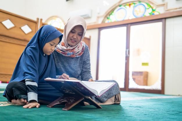 Femme musulmane avec enfants lisant le coran ensemble
