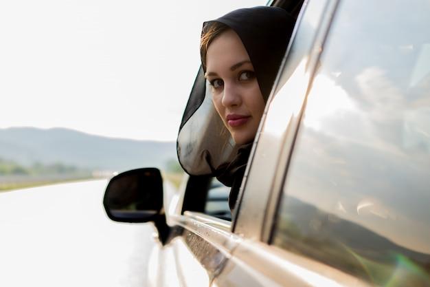 Femme musulmane à l'extérieur de la fenêtre de la voiture