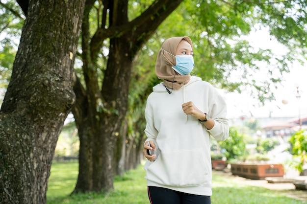 Femme musulmane faisant du sport et utilisant un masque en plein air pour empêcher la propagation du virus