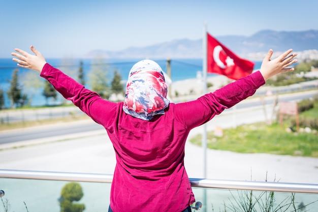 Femme musulmane heureuse au parc de l'hôtel avec le drapeau turc derrière elle